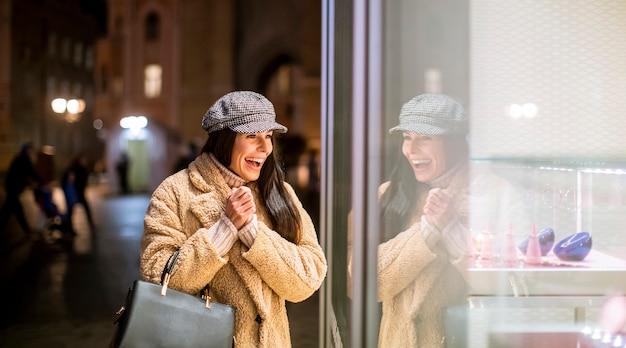 Mulher jovem e bonita perto da vitrine na época do natal