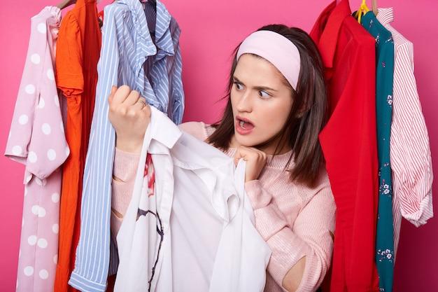 Mulher jovem e bonita perto de prateleira com ganchos. senhora chocada encontra mancha horrível na blusa branca. morena feminina detém camisa. menina vai às compras. menina usa camisola no shopping. roupas coloridas na loja.
