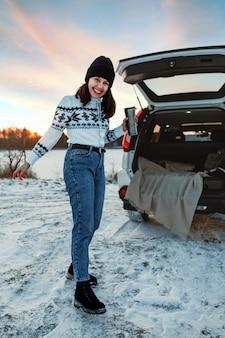 Mulher jovem e bonita perto de um carro suv com o porta-malas aberto ao pôr do sol na praia do lago congelado
