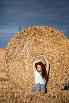 Mulher jovem e bonita perto de um feixe de feno em um campo. férias na aldeia, uma menina curtindo a natureza em um campo ceifado em um dia ensolarado