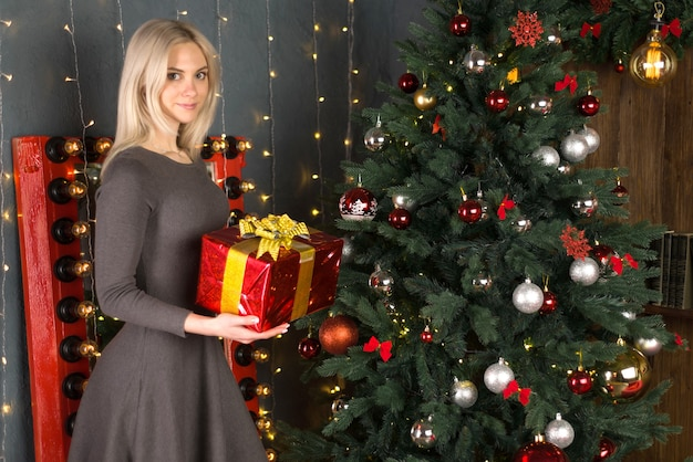 Mulher jovem e bonita perto de uma árvore de natal segurando uma caixa de presente