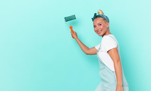 Mulher jovem e bonita pintando uma parede com um rolo