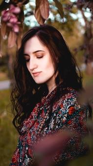 Mulher jovem e bonita por ramos com folhas verdes e cor de vinho Foto Premium