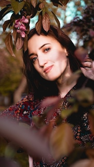 Mulher jovem e bonita por ramos com folhas verdes e cor de vinho