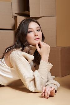 Mulher jovem e bonita posa entre caixas de papelão. retrato da moda da beleza, entrega de encomendas, mover-se com as coisas nas caixas