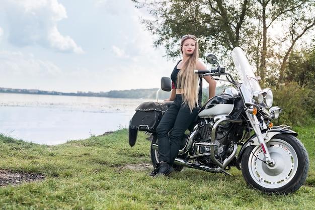 Mulher jovem e bonita posando com moto do lado de fora