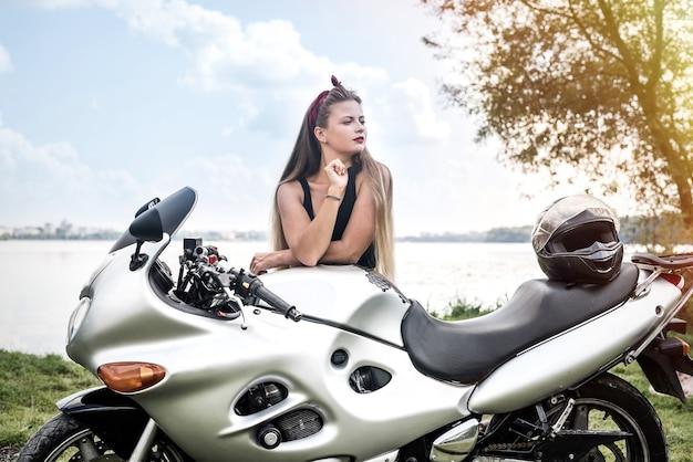 Mulher jovem e bonita posando com moto lá fora