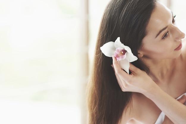 Mulher jovem e bonita posando com orquídea. tratamento de cuidados com a pele.
