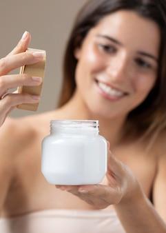 Mulher jovem e bonita posando com um produto para a pele