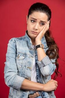 Mulher jovem e bonita posando de jaqueta jeans em um fundo vermelho. foto de alta qualidade