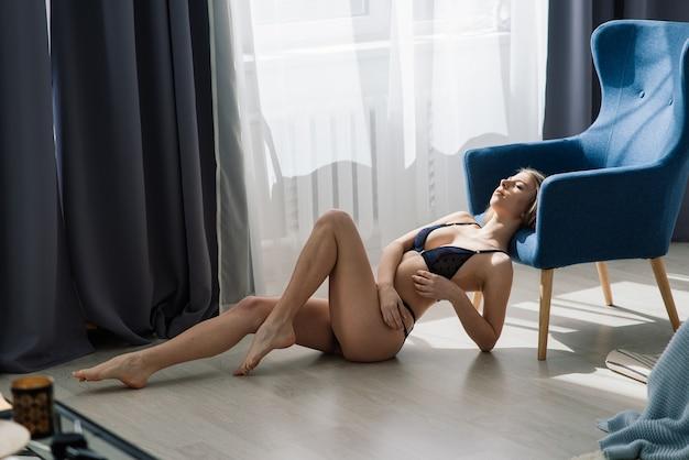 Mulher jovem e bonita posando de lingerie sexy preta. interior vintage e fundo retro.