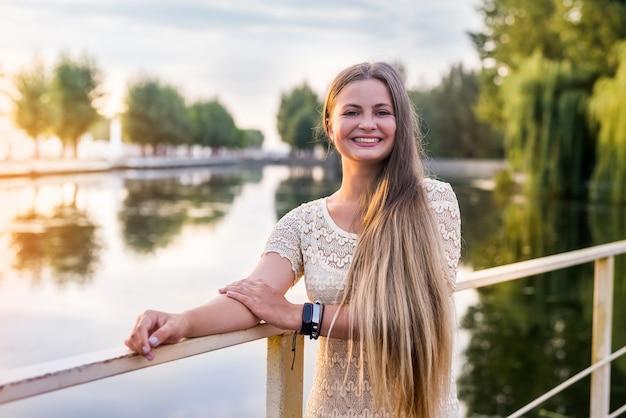 Mulher jovem e bonita posando em um vestido longo no cais
