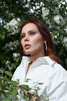 Mulher jovem e bonita posando perto da árvore da flor de cerejeira