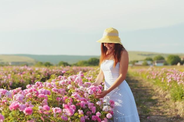 Mulher jovem e bonita posando perto de rosas em um jardim.