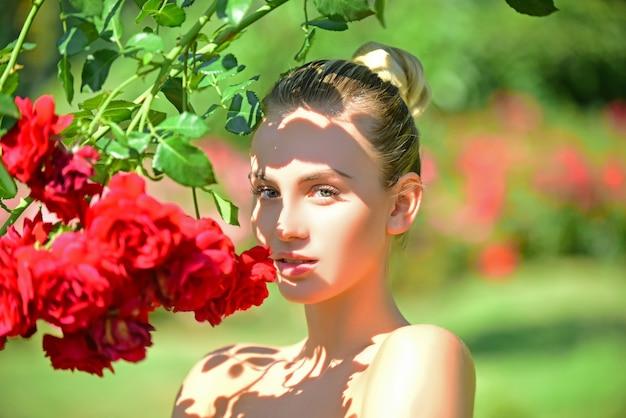 Mulher jovem e bonita posando perto de rosas em uma garota de jardim de verão andando no jardim de rosas vermelhas