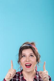 Mulher jovem e bonita positiva com brincos vermelhos mostra alegremente o dedo para cima, posando em um azul