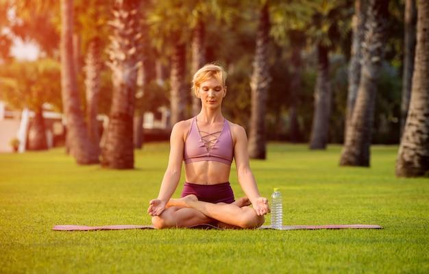 Mulher jovem e bonita pratica ioga na praia. exercício de manhã cedo. água potável. nascer do sol