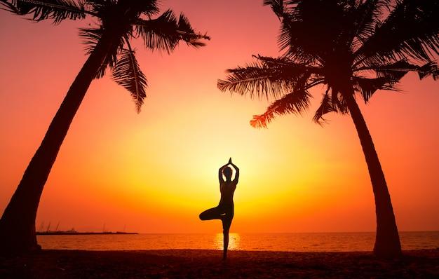 Mulher jovem e bonita pratica ioga na praia. exercício de manhã cedo. nascer do sol