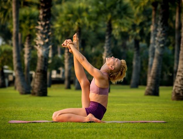 Mulher jovem e bonita pratica ioga na praia. exercício de manhã cedo