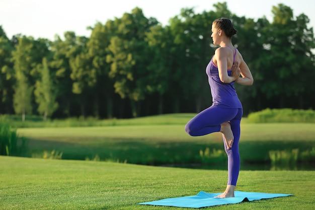 Mulher jovem e bonita praticando ioga ao ar livre pela manhã
