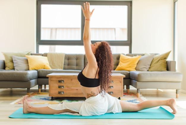 Mulher jovem e bonita praticando ioga em ambientes fechados