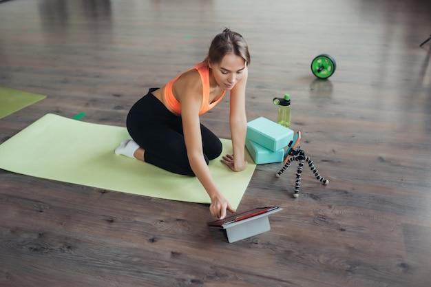 Mulher jovem e bonita praticando ioga, está envolvida com o professor online através de um tablet. conceito de esportes em casa.