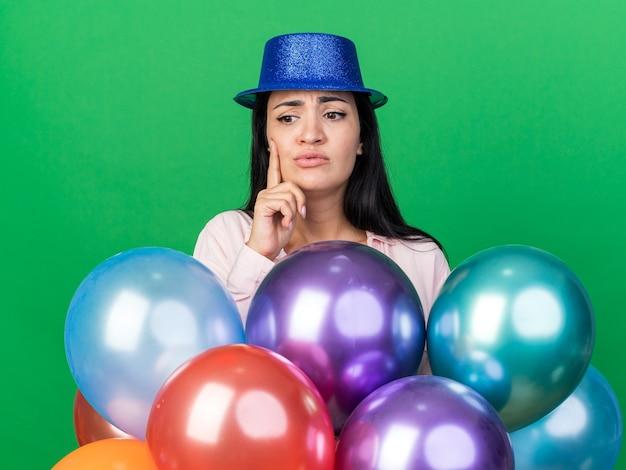 Mulher jovem e bonita preocupada com chapéu de festa em pé atrás de balões, colocando o dedo na bochecha isolada na parede verde