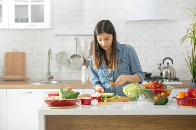 Mulher jovem e bonita preparando uma salada vegetariana de vários vegetais no interior da cozinha em cores claras.