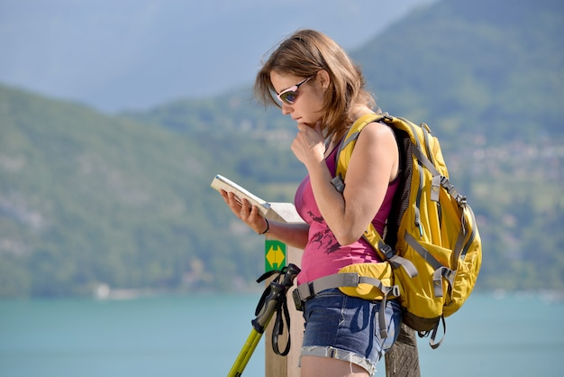 Mulher jovem e bonita, procurando o caminho para uma caminhada na montanha
