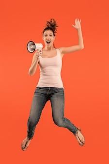 Mulher jovem e bonita pulando com o megafone isolado sobre fundo vermelho.