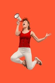 Mulher jovem e bonita pulando com o megafone isolado sobre o vermelho.