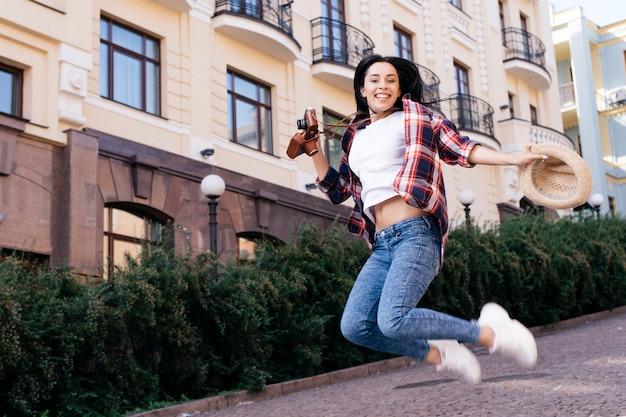 Mulher jovem e bonita pulando na rua com segurando o chapéu e a câmera