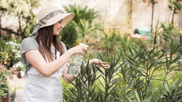 Mulher jovem e bonita pulverização de água da garrafa em plantas a crescer