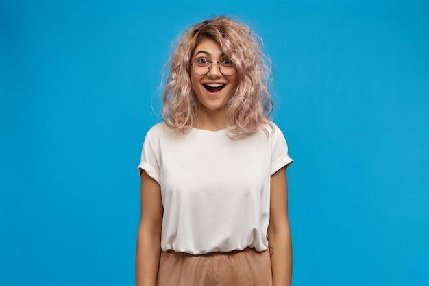 Mulher jovem e bonita radiante, vestindo uma camiseta branca enorme e óculos redondos, feliz por receber notícias positivas inesperadas, abrindo a boca amplamente