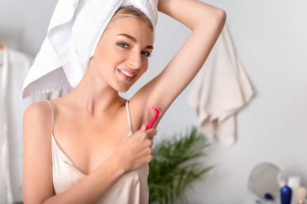 Mulher jovem e bonita raspando as axilas em casa