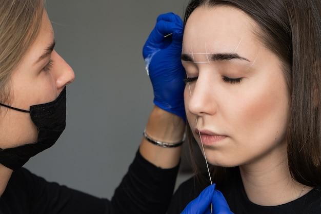 Mulher jovem e bonita recebe procedimento de correção de sobrancelha.