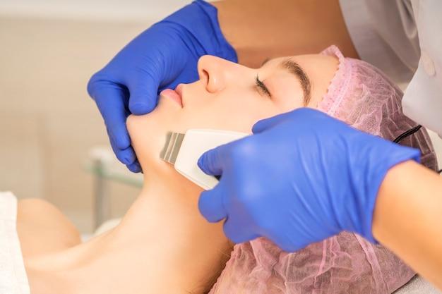 Mulher jovem e bonita recebendo cavitação ultra-sônica para limpeza facial em salão de beleza
