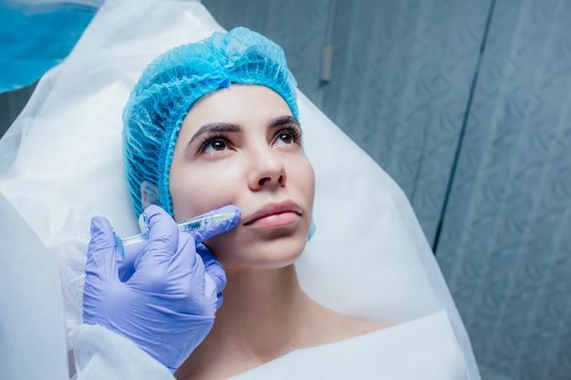Mulher jovem e bonita recebendo injeção cosmética de botox nos lábios