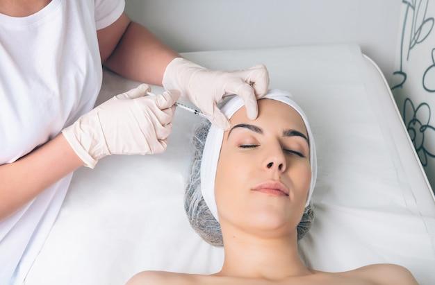 Mulher jovem e bonita recebendo injeção plástica no rosto como parte do tratamento clínico. conceito de medicina, saúde e beleza.