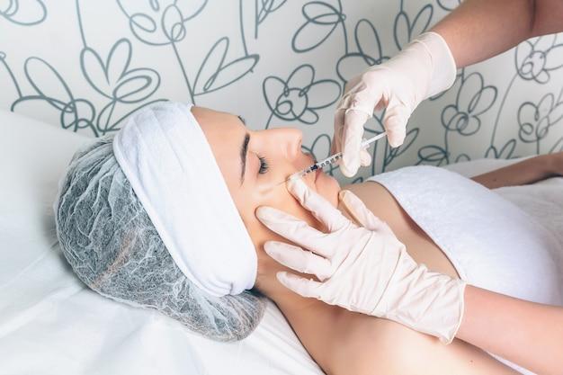 Mulher jovem e bonita recebendo injeção plástica nos lábios como parte do tratamento clínico. conceito de medicina, saúde e beleza.