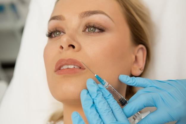 Mulher jovem e bonita recebendo injeções de beleza na cara dela