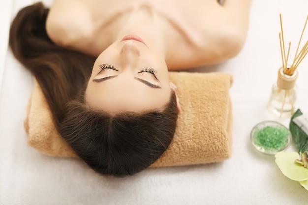 Mulher jovem e bonita recebendo massagem facial deitada no sofá
