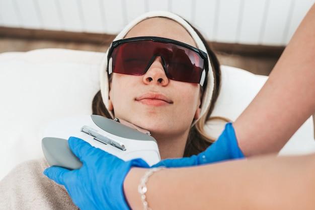 Mulher jovem e bonita recebendo procedimento de cosmetologia de remoção de cabelo na clínica de spa de beleza cosmética.