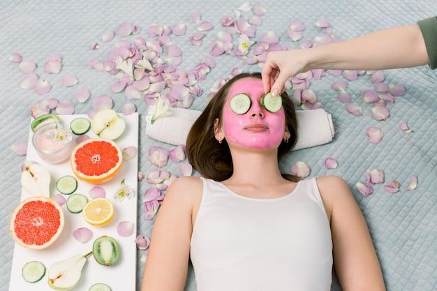 Mulher jovem e bonita recebendo tratamento de spa com máscara cosmética rosa e fatias de pepino nos olhos, cuidados com a pele, antienvelhecimento, acne