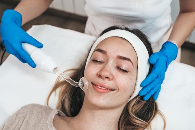 Mulher jovem e bonita recebendo tratamento facial de limpeza e rejuvenescimento em um salão de beleza spa. esfoliação e tratamento de hidratação.