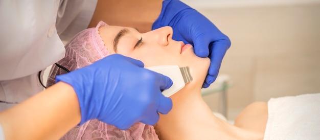 Mulher jovem e bonita recebendo ultrassom cavitação facial em salão de beleza