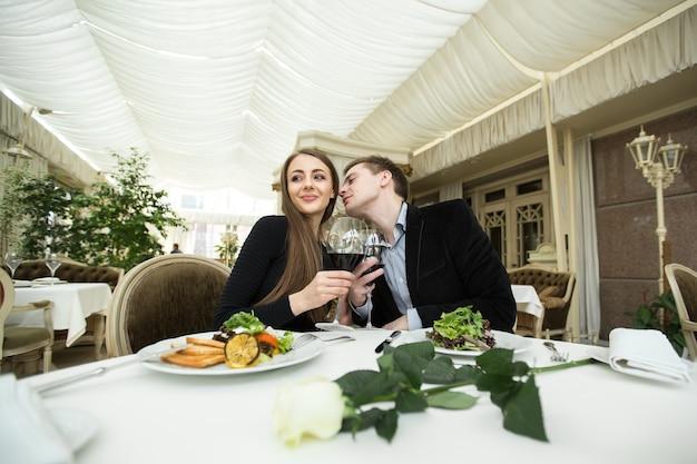 Mulher jovem e bonita recebendo um beijo na bochecha enquanto comia com o namorado em um restaurante