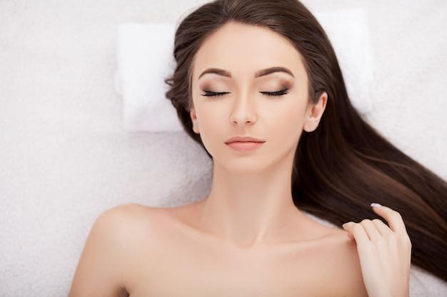 Mulher jovem e bonita recebendo um tratamento de rosto no salão de beleza