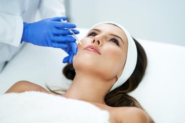 Mulher jovem e bonita recebendo um tratamento facial de ácido no salão de beleza.
