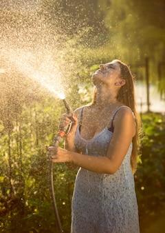 Mulher jovem e bonita regando o jardim com mangueira